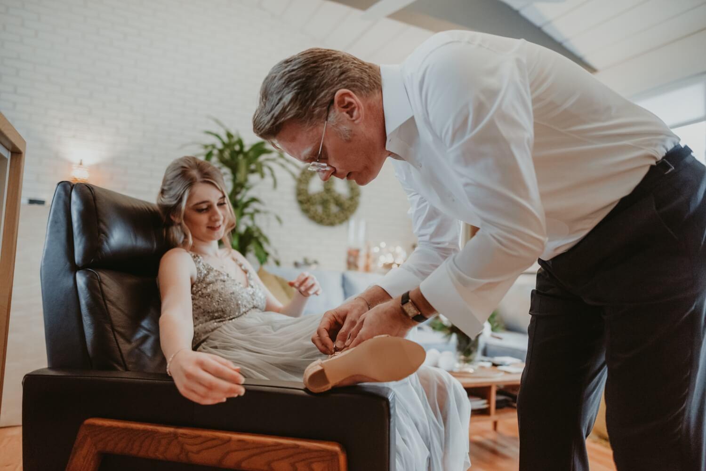 groom helping bridesmaid to tie her shoe - the Adamkovi - Chicago wedding photography