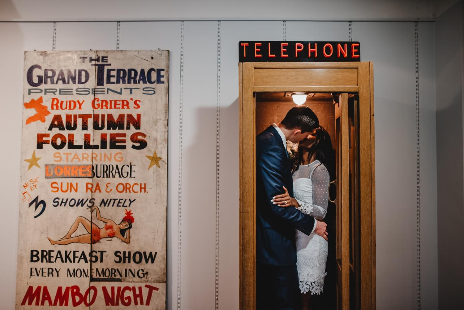 Chicago City Hall Wedding Photographer - The Adamkovi, bride and groom kissing in a telephone booth, mixed couple
