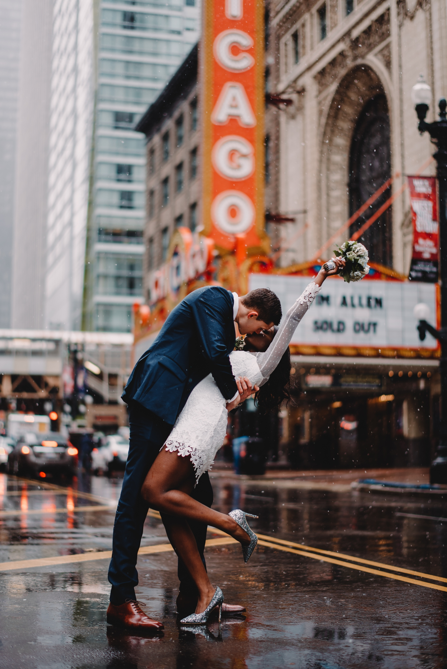 Chicago City Hall Wedding Photographer - The Adamkovi, bride and groom in front of the Chicago theater in the middle of the street, kiss dip, mixed couple