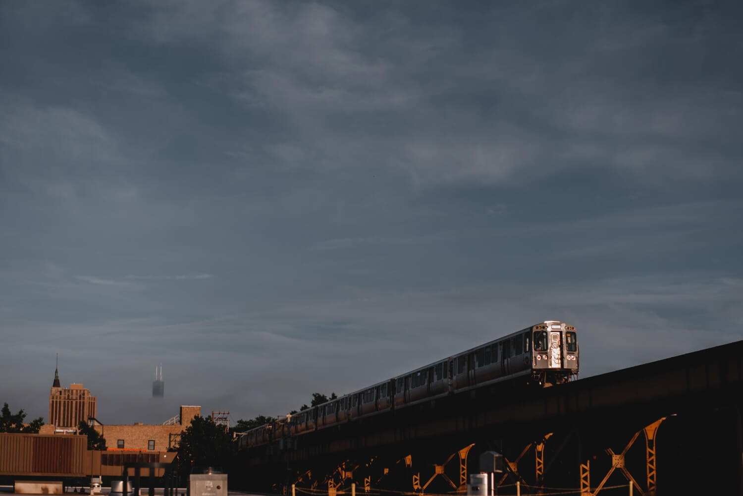 Logan Square Chicago Engagement Photographer, photo fo the L train with city skyline in the background, Blue line
