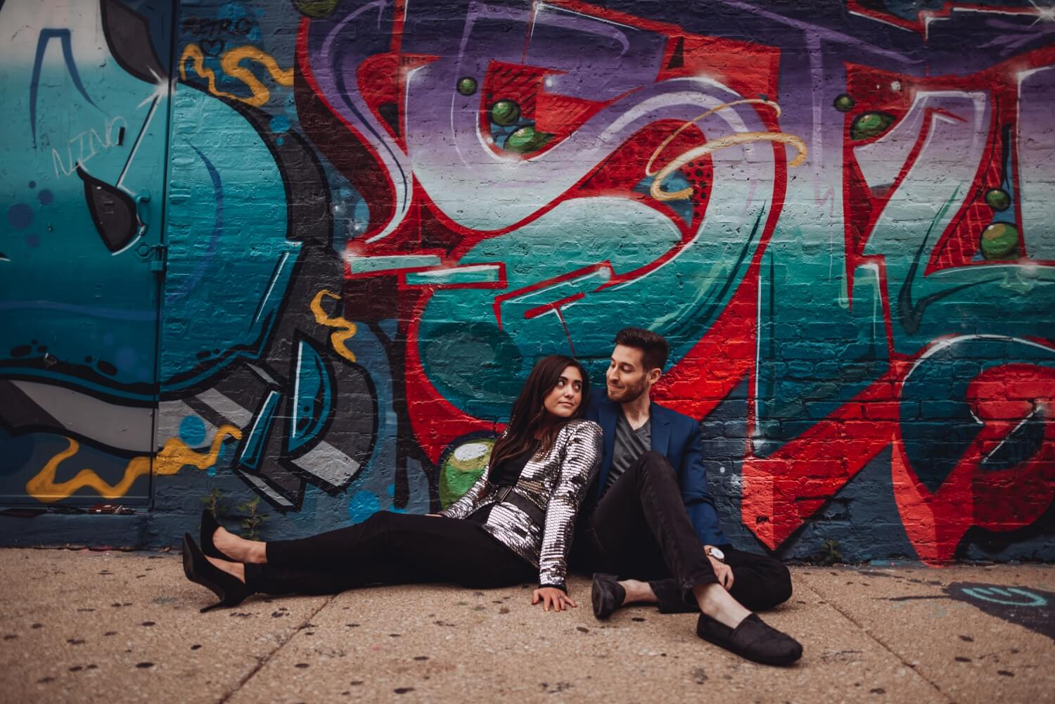 Wicker Park Engagement Photographer - The Adamkovi, couple sitting in front of graffiti wall.