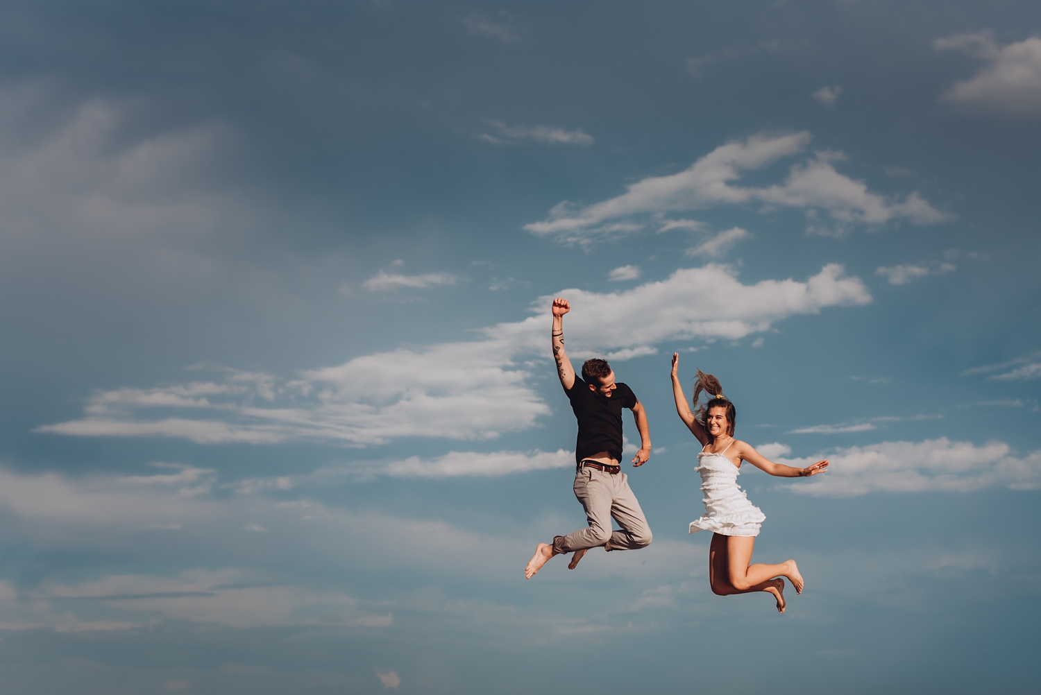 North Avenue Chicago Engagement - The Adamkovi, jumping couple with sky behind them