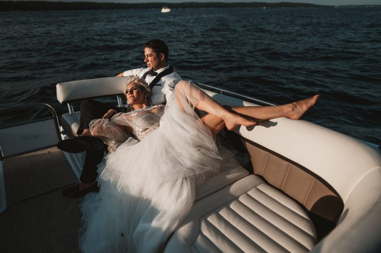 Lake Geneva Micro Wedding - The Adamkovi bride and groom photos on a boat bride lying, long legs